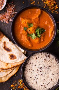 A bowl of curry, rice and naan bread